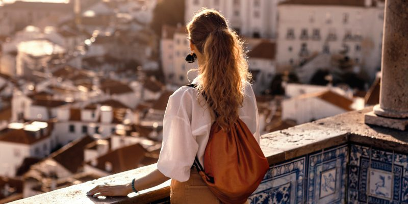 Scene with a female tourist who is walking on the street of Iberic city and poses in a famous, most recognizable places with breathtaking view